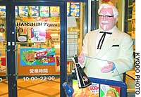 A Colonel Sanders statue holding a plastic Hanshin Tigers megaphone stands at the entrance of a Kentucky Fried Chicken outlet near Koshien Stadium.