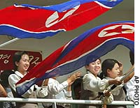 Female crew members wave the North Korean flag aboard the Mangyongbong-92 ferry as it arrives at Niigata port.