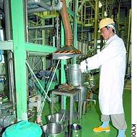 A JCO employee demonstrates how workers at its nuclear fuel processing plant in Tokai, Ibaraki Prefecture, used metal buckets to mix uranium solution.