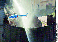 A helicopter circles above a Nippon Steel Corp. gas tank in Tokai, Aichi Prefecture, that is being doused with water after exploding the night before.