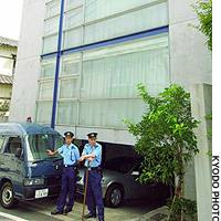 Police stand guard outside the home of Deputy Foreign Minister Hitoshi Tanaka in Meguro Ward, Tokyo, after an explosive device was found there.