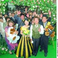 Friends celebrate with Akio Fuwa and Saki Kimura at their wedding in Kobe on Saturday. The couple -- ardent Hanshin Tigers fans -- based their wedding attire on the baseball team's uniforms.