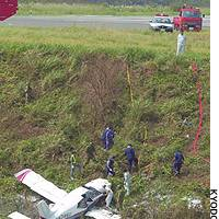 Officials inspect a single-engine plane after it crashed at an airport in Mitsushima, in the Tsushima islands in Nagasaki Prefecture.