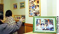 Visitors view photographs of a Tokyo family found stabbed to death at their Setagaya Ward home on New Year's Eve, 2000.