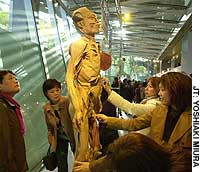 Women touch an actual corpse in the 'Mysteries of the Human Body' exhibition at the Tokyo International Forum in Chiyoda Ward.