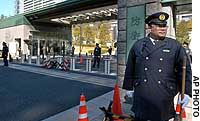 Police stand guard outside the Defense Agency in Tokyo.