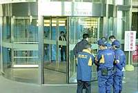 Investigators gather Friday at the Mori Tower building in the Roppongi Hills complex in Minato Ward, Tokyo, where a child was fatally injured after getting his head jammed in the revolving doors.