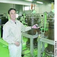 Kazuharu Yoshizuka of the University of Kitakyushu holds a vial containing a special extraction agent that makes it possible to draw lithium from seawater at a plant in the city of Imari, Saga Prefecture.