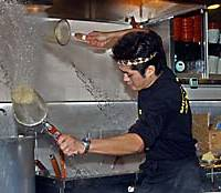 Konosuke Taekewaka whips a sieve of ramen noodles through the air to shake out the water at Shiodome Ramen in Tokyo's Minato Ward.