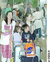 Holidaymakers arrive at Kansai airport, among some 16,000 expected to return from abroad Tuesday.