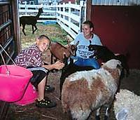 A boy living on Green Chimneys' farm 'campus' juvenile rehabilitation  center in Brewster, New York takes care of animals with a female employee.