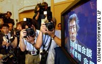 Photojournalists snap pictures of a TV broadcasting Prime Minister Junichiro Koizumi's news briefing in Pyongyang after his meeting with North Korean leader Kim Jong Il.