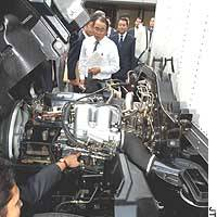 An official representing a 10-company consortium showcases a clean-air engine for trucks during a recent media preview in Tokyo. The engine is powered by dimethyl ether produced from natural gas.