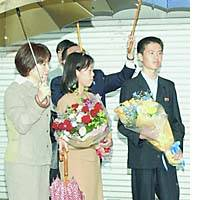 Shigeyo Hasuike (second from left) and her brother, Katsuya, hold flowers given by locals on May 23 as their mother, Yukiko (left), looks on.