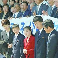 The three children of Yasushi and Fukie Chimura — Kiyoshi (second from left), Emi (center) and Yasuhiko (second from right) — are greeted by local people upon their arrival here May 24.