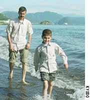 Mohamad Haytham Saleh, accompanied by his father, Haytham, enjoys his first ever walk in the ocean Saturday.