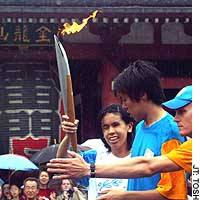 Kozue Matsumoto of Chiba Prefecture, who has been blind since the age of 2, starts her run carrying the Olympic flame in front of Kaminarimon gate in Tokyo's Asakusa district Sunday.