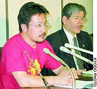Nobutaka Watanabe (left) speaks to reporters in Tokyo after filing a lawsuit against the government.