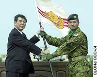 Ground Self-Defense Force Col. Koichiro Bansho returns the flag of the first batch of troops sent to Iraq to Defense Agency head Shigeru Ishiba at a ceremony in Asahikawa, Hokkaido.