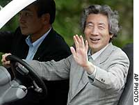 Prime Minister Junichiro Koizumi drives his own cart to the afternoon plenary session of the Group of Eight summit in Sea Island, Georgia.