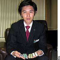 Shigeyoshi Mori, a certified medical representative at Sawai Pharmaceutical Co. in Tokyo, displays his firm's drugs.