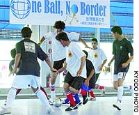 Kurdish Turks seeking asylum in Japan, in white, square off Sunday against another team during a futsal tournament in Chofu, western Tokyo.