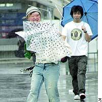 A woman in Osaka struggles with her umbrella Monday as strong wind from Typhoon Dianmu buffets western Japan.