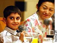 Mohamad Haytham Saleh, a 10-year-old Iraqi boy who came to Japan to receive treatment on an injured eye, speaks at a news conference Monday in Tokyo. Yukiko Hashida, the widow of a slain Japanese journalist who worked to make the trip possible, looks on.