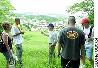 U.S. Marine Corps personnel listen to a guide's explanation on a hill where the ruins of Usasoe Castle are located, during a tour of sites related to the Battle of Okinawa.