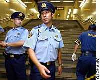 Police patrol a Shibuya subway station stairway after a station worker was shot and wounded by an unidentified man during the morning rush hour.