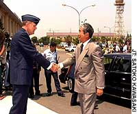 Tokyo Gov. Shintaro Ishihara is greeted in June 1999 by Air Force Gen. John Hall, then commander of U.S. forces in Japan, when he visited Yokota Air Base.