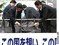 Security officers for Prime Minister Junichiro Koizumi attach bulletproof sheets along the rooftop deck of a campaign vehicle ahead of the start of his stumping activities for the House of Councilors election.
