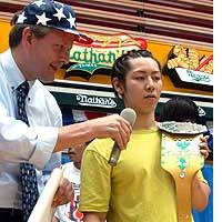 Takeru Kobayashi holds a champion belt during the Japanese qualifying contest in Tokyo for the annual Fourth of July hot dog wolfing contest at New York's Coney Island.