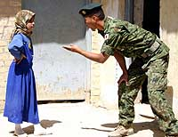 A Ground Self-Defense Force soldier talks to a local girl on the street in the southern Iraqi city of Samawah. | GROUND SELF-DEFENSE FORCE PHOTO
