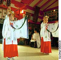 Two shrine maidens at Kumano Hayatama Taisha shrine in Shingu, Wakayama Prefecture, perform a celebratory dance Thursday evening, with the holy grounds and a pilgrimage site in the area having been designated a World Heritage site.