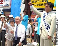 Teruaki Masumoto (right) calls for voter support in front of Tokyo's Iidabashi Station on June 24 as relatives of abductees rally for him.