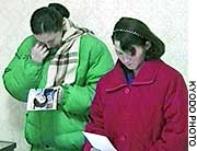 Mika and Belinda Jenkins, daughters of Hitomi Soga and Charles Robert Jenkins, look at photos of their mother in this November 2002 file photo from Pyongyang.