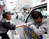 A candidate in the July 11 House of Councilors election leans out of his campaign vehicle to greet a passerby in Tokyo's Asakusa district.