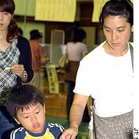 A boy helps his mother vote in the House of Councilors election Sunday in Minato Ward, Tokyo.