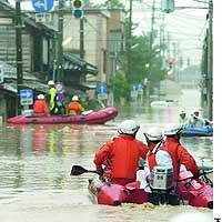 Firefighters travel by boat to rescue people who have been left stranded by floods brought about by heavy rain in Sanjo, Niigata Prefecture.