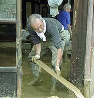 A man clears mud and debris from his home in the town of Nakanoshima, Niigata Prefecture.