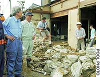 Prime Minister Junichiro Koizumi speaks to residents in Nakanoshima, Niigata Prefecture, as they engage in cleanup work following heavy flooding.