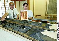 Researchers at the Nara National Research Institute for Cultural Properties display pieces of timber from the ceiling of the main hall of Horyuji Temple, shown below.