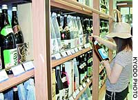 Shoppers view bottles of `shochu' at a department store in Kagoshima.