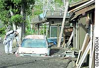A man checks a car stuck in volcanic mud in the Miike district of Miyake Island on Tuesday.