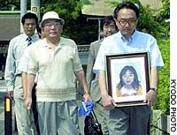 Relatives of those who died in a fatal overpass crush in July 2001 make their way toward the Kobe District Court.