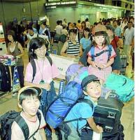 A family at Narita airport prepares to leave on an overseas trip amid the peak of the summer exodus.