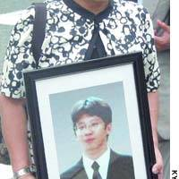 The mother of Kuniaki Uranaka carries a portrait of her son, who was killed by mobsters in 2002, as she enters the Kobe District Court on Thursday for the sentencing of her son's killers.