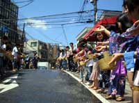 People water a street in Tokyo's Shibuya Ward to help ease the heat during a recent event organized by citizens' groups. | PHOTO COURTESY OF OPERATION UNIT OF UCHIMIZU