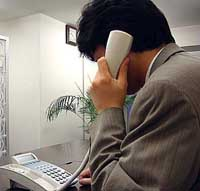 A counselor of Peacemind Inc. offers advice over the phone to a Japanese living abroad at the firm's Tokyo office. | PHOTO COURTESY OF PEACEMIND INC.